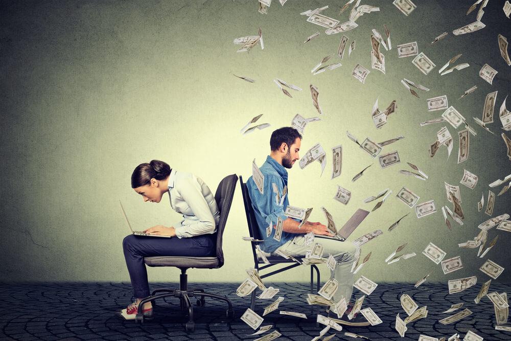 chica y chico sentados de espaldas con ordenador y billetes volando