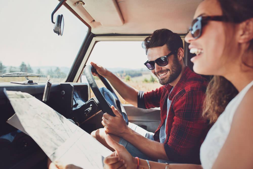 Mädchen und Junge sitzen im Auto und schauen auf eine Karte