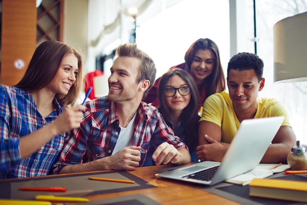 grupo de jóvenes trabajando juntos con ordenador y rotuladores
