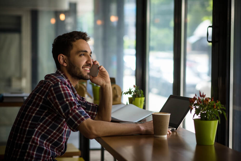 Junger Mann sitzt in einem Kaffee und telefoniert