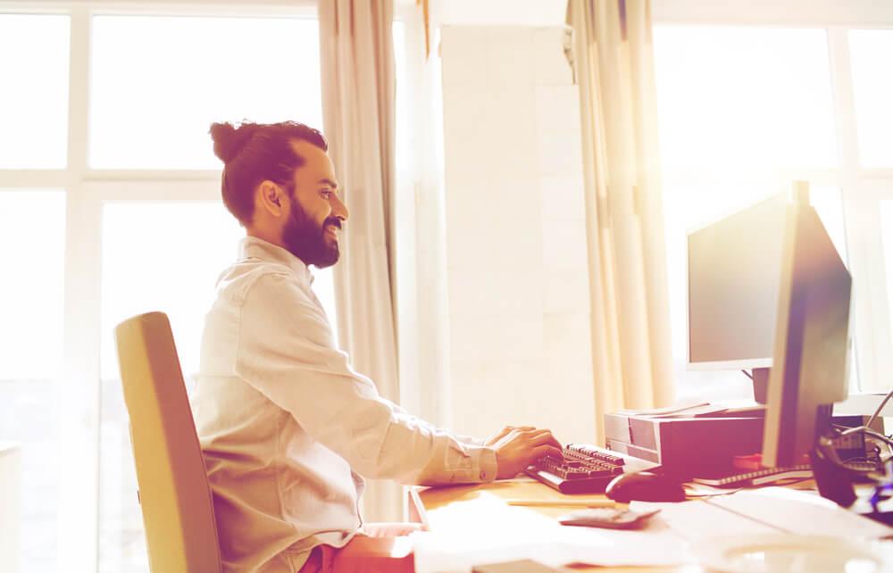 Mann sitzt am Schreibtisch und schreibt auf seinem Computer