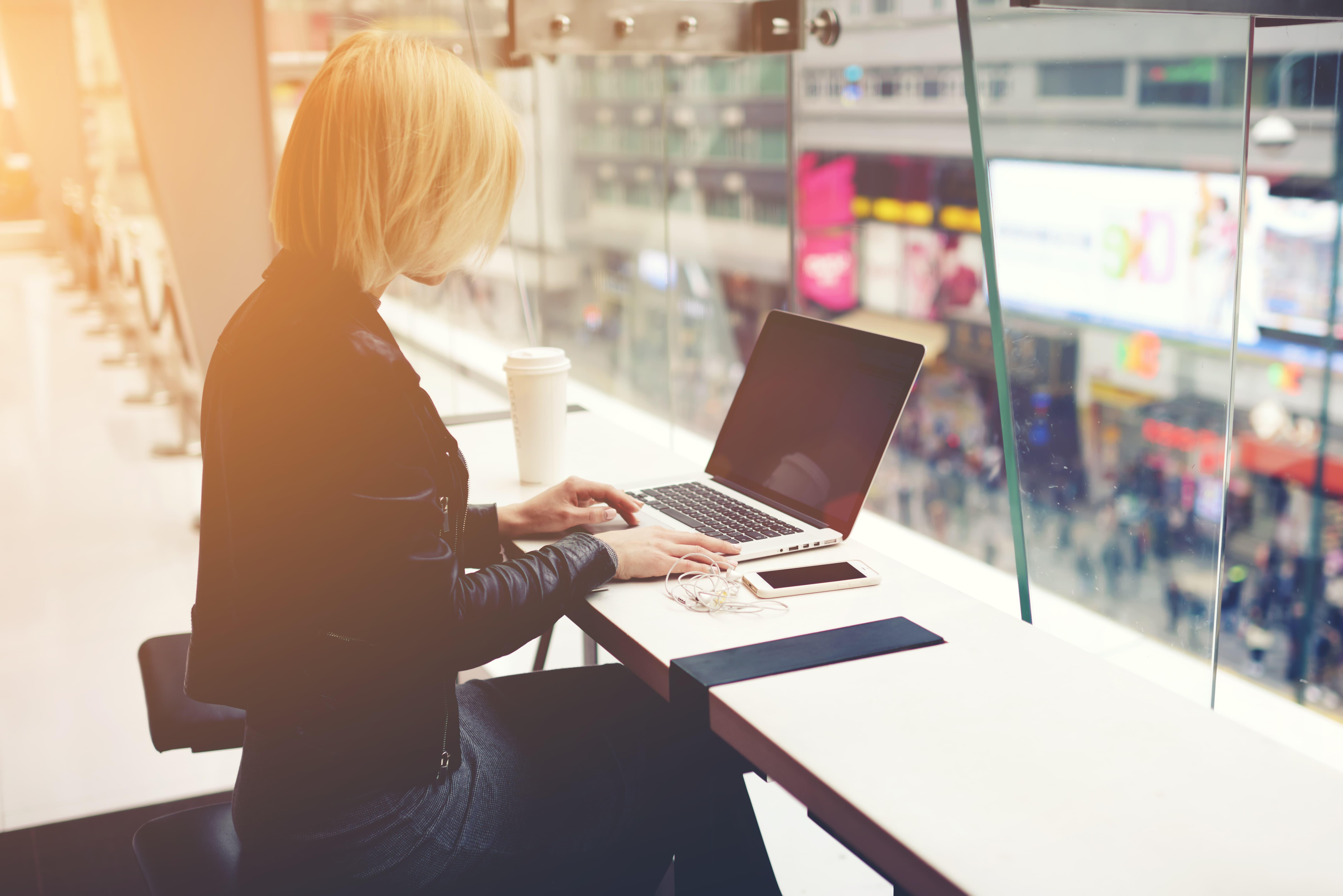 Frau sitzt vor einen Laptop