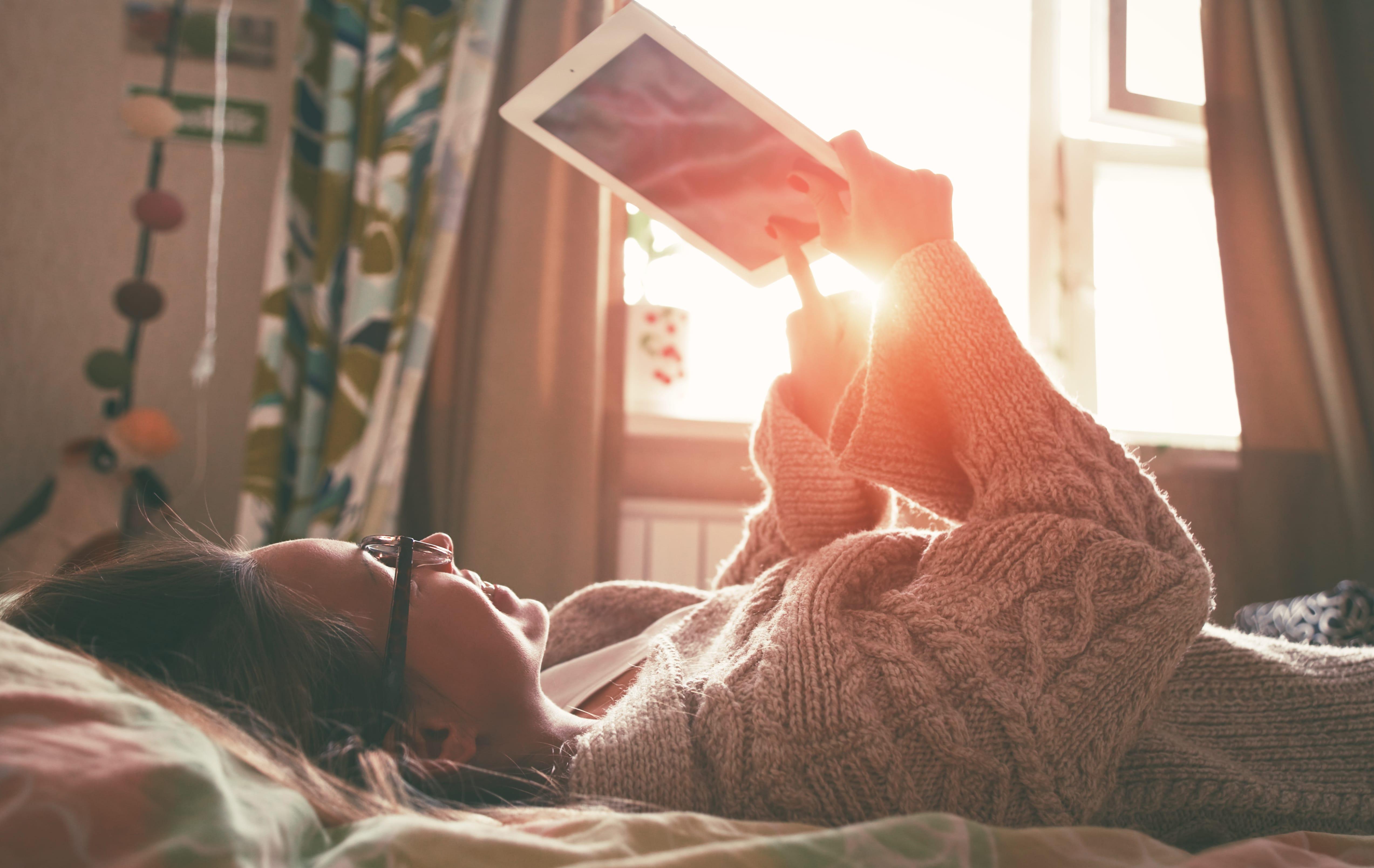 Mädchen liegt im Bett mit ihrem Tablet
