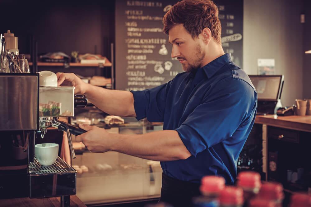 Mann macht an einer Kaffee Maschine Espresso