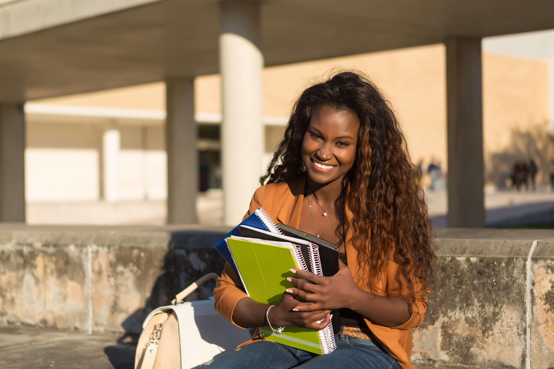 chica joven con cuadernos en la calle