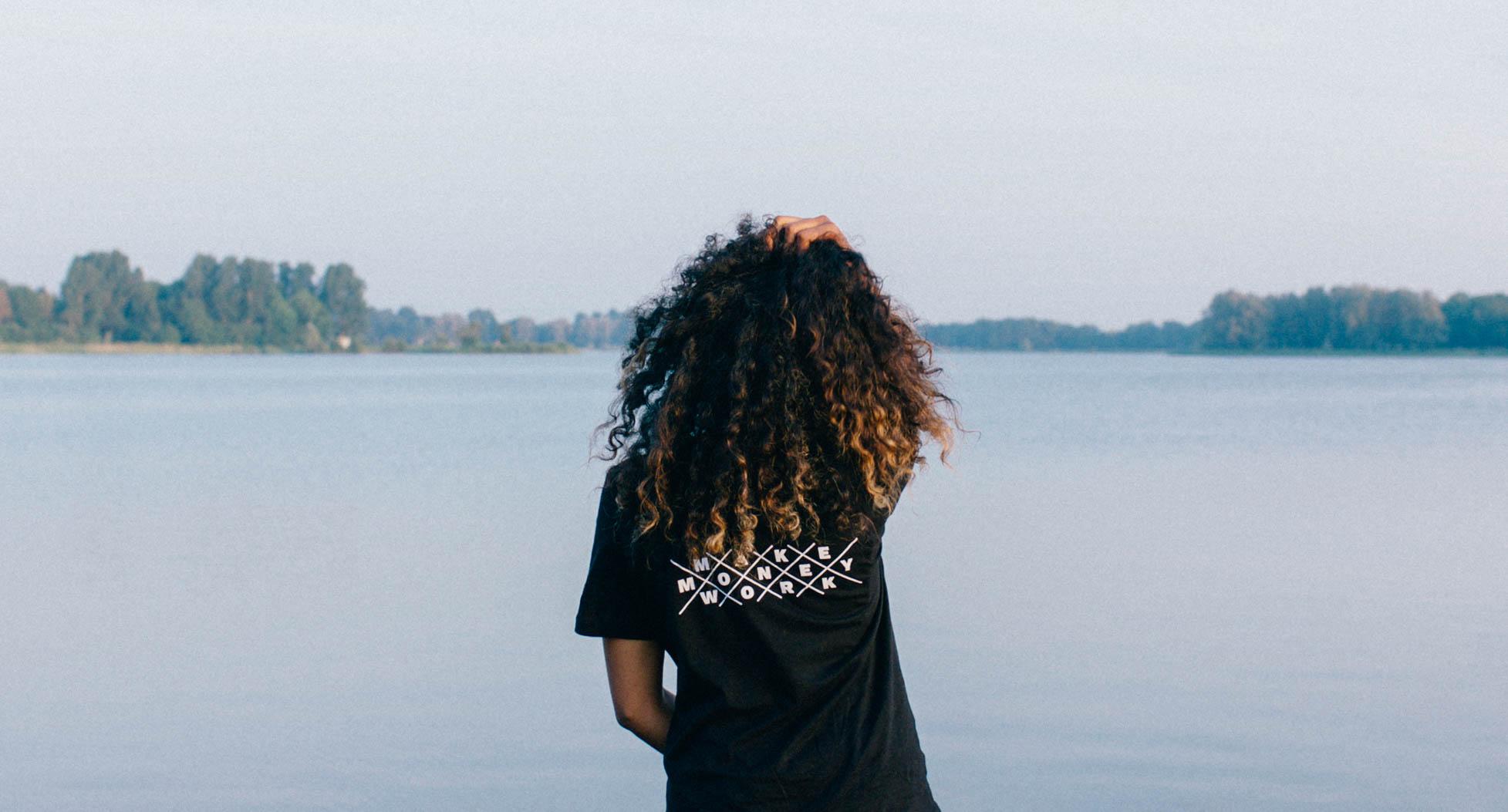 Frau fährt sich vor einem See durch die Haare