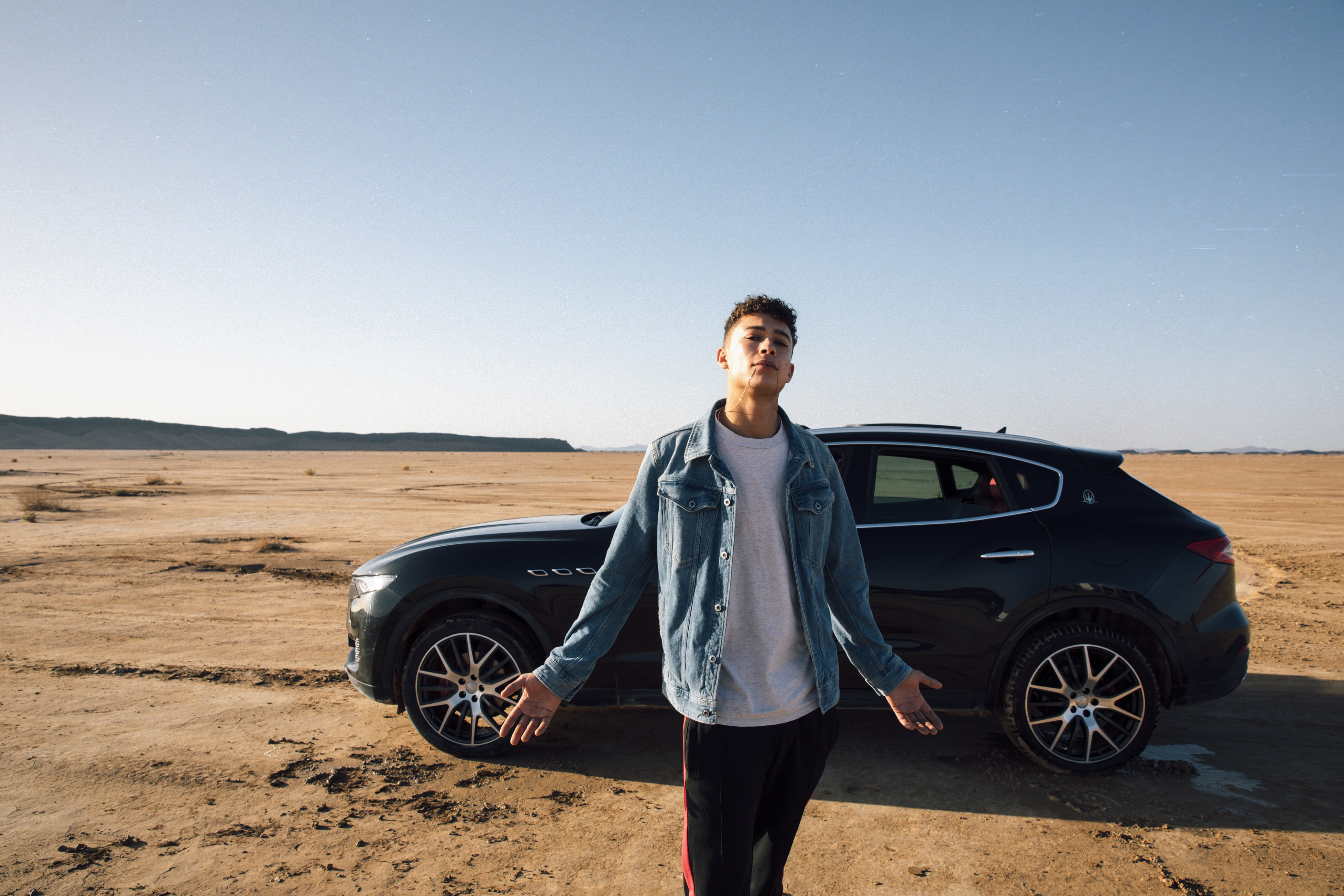 A young adult standing in front of a car in a desert