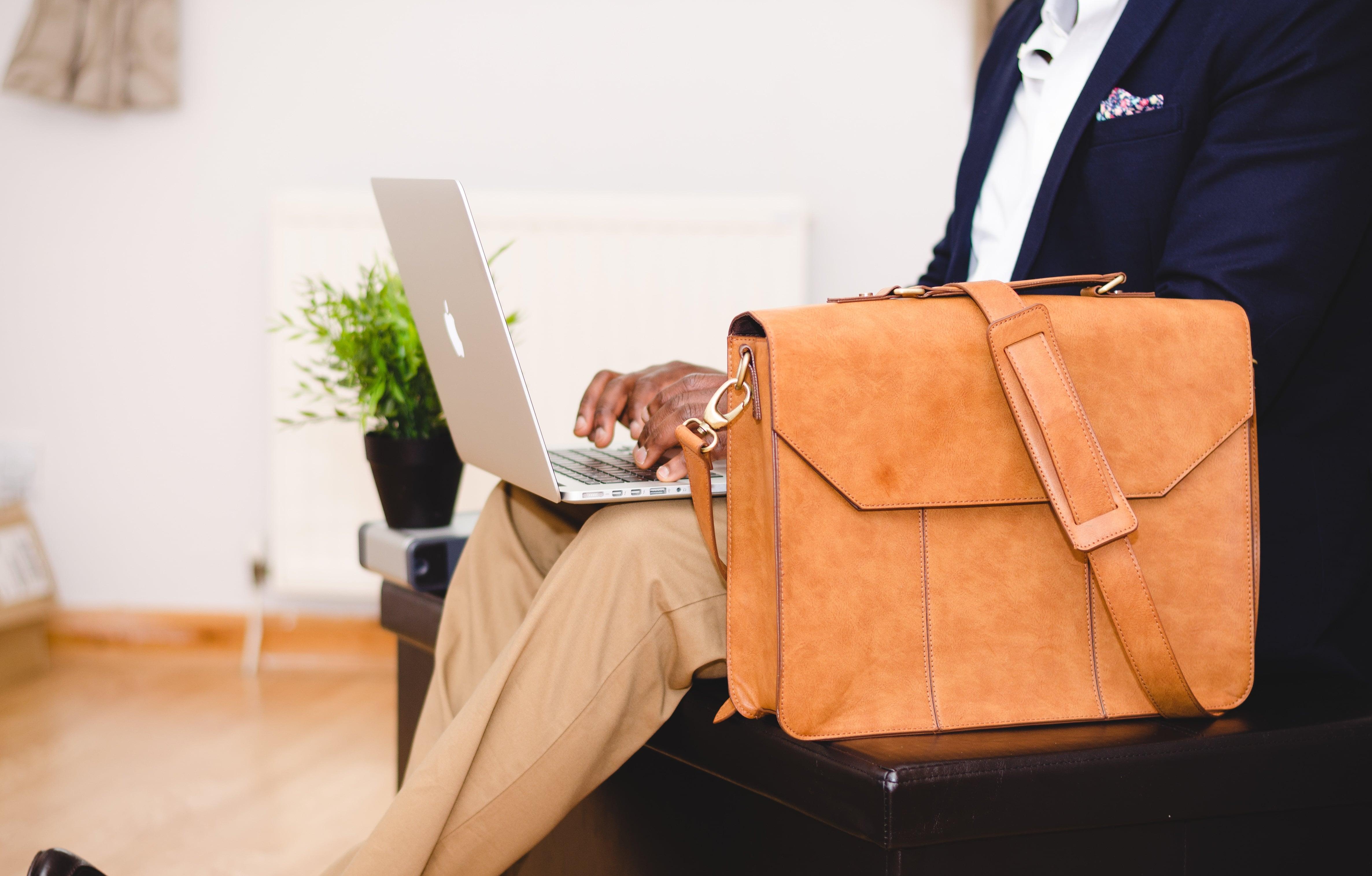 Mann tippt auf Laptop auf dem Schoß und die Tasche steht daneben