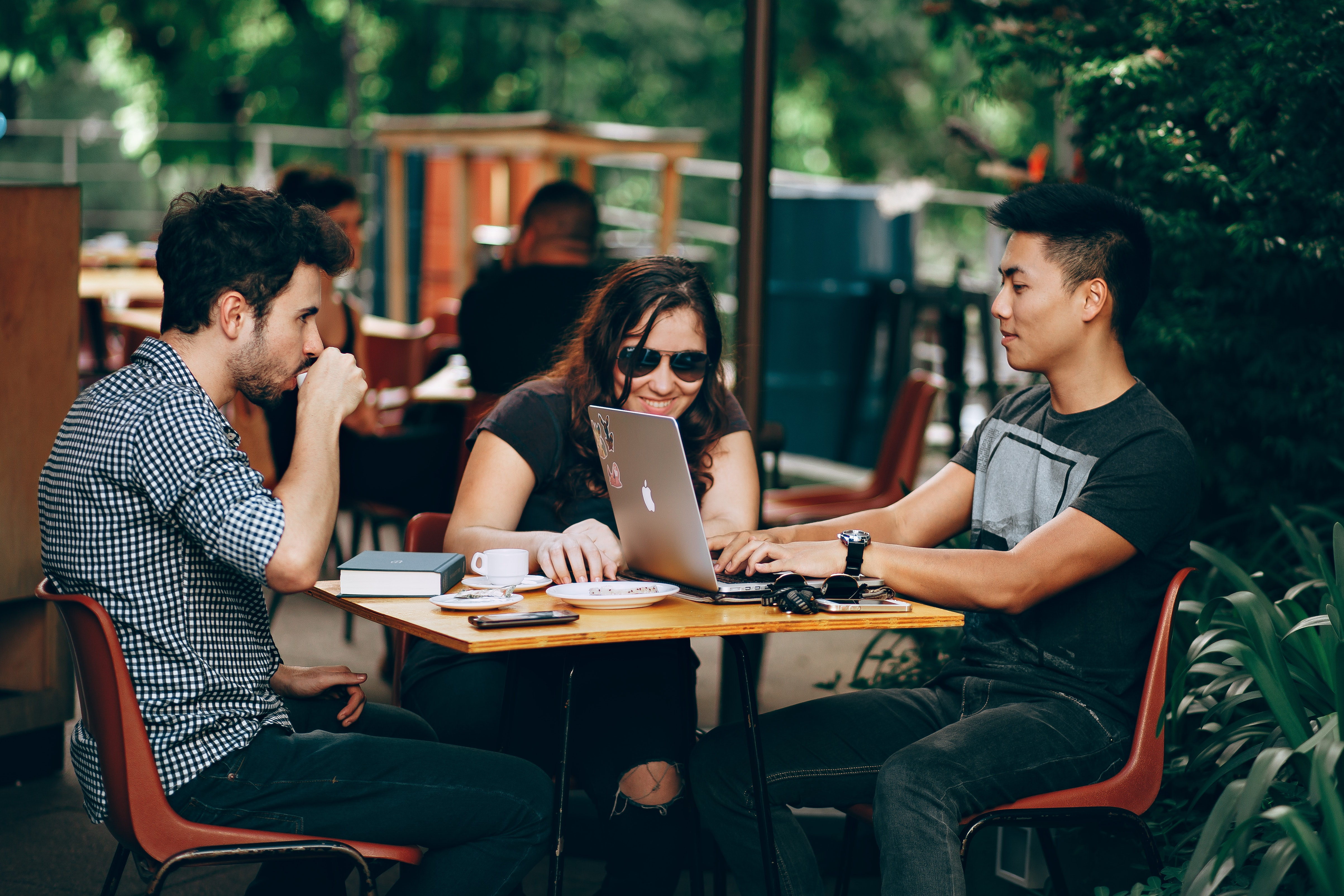 drei junge Leute am Tisch im Café