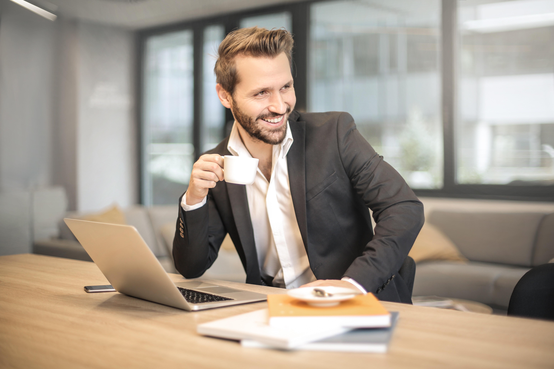 Glücklicher Mann arbeitet am Laptop
