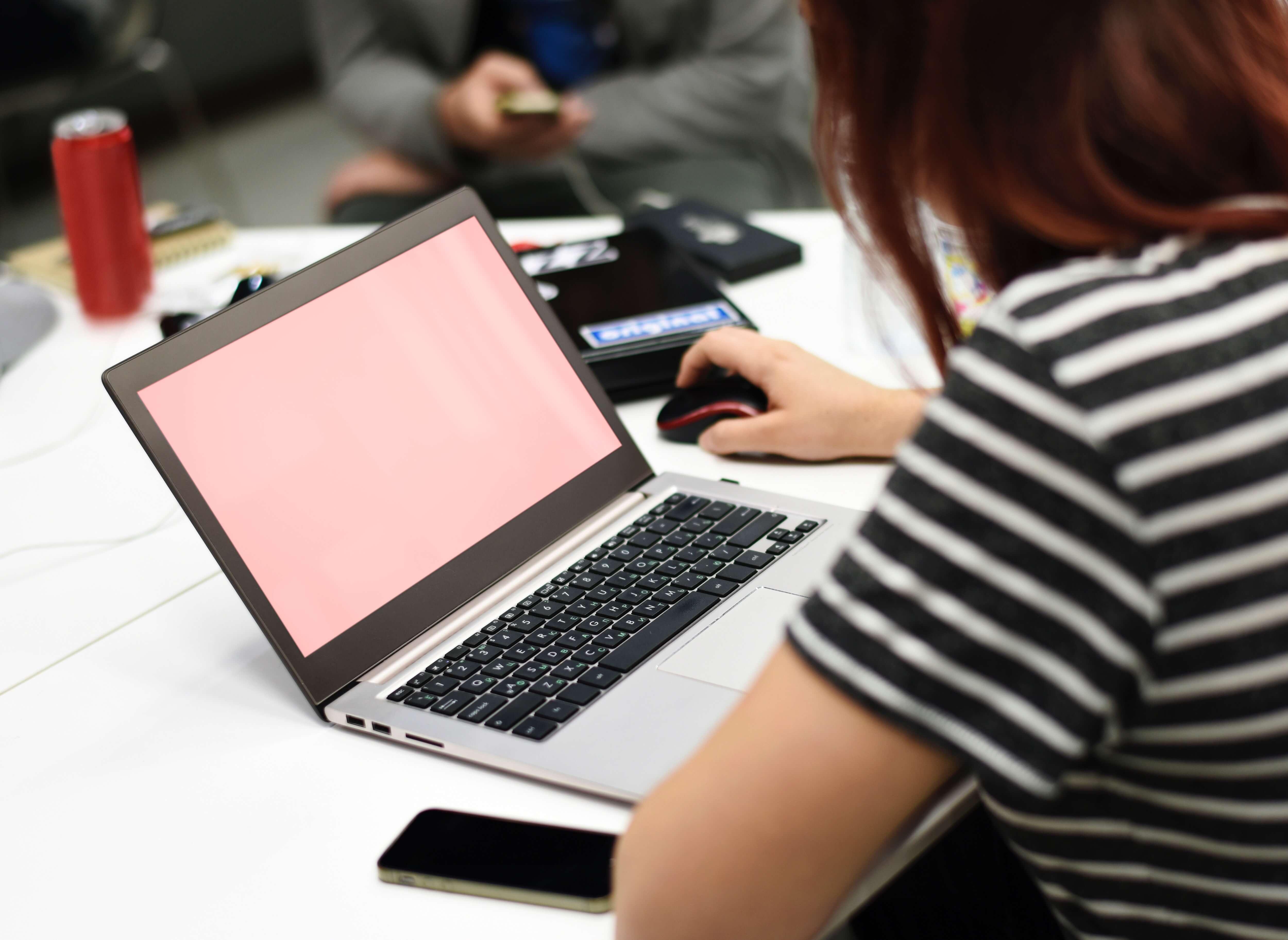 Frau sitzt an einem Tisch und arbeitet mit einem Computer