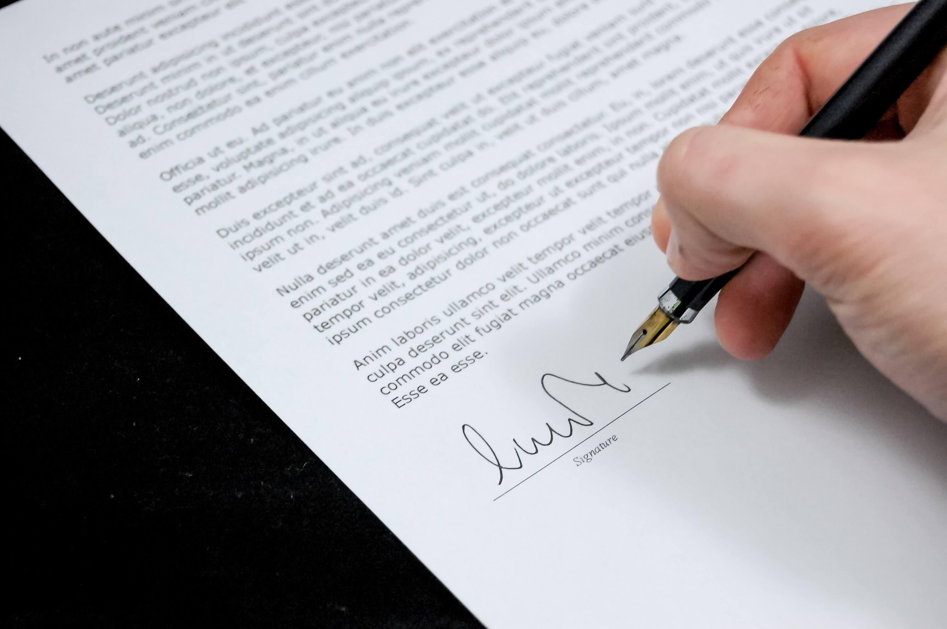 Jemand unterschreibt ein Dokument