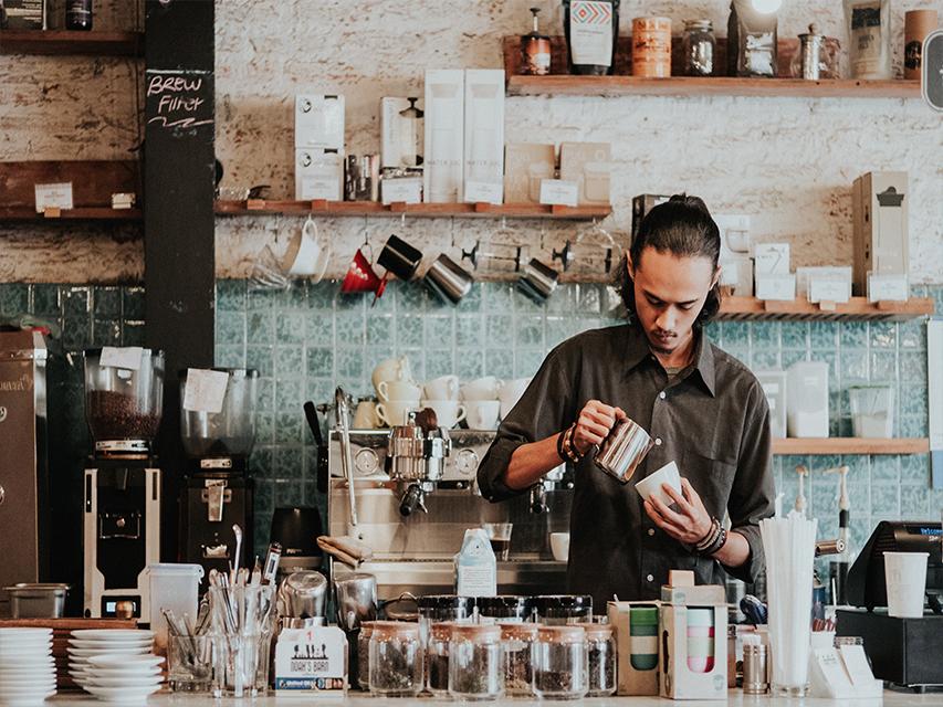 Ein Mann steht hinter der Theke und macht Kaffee