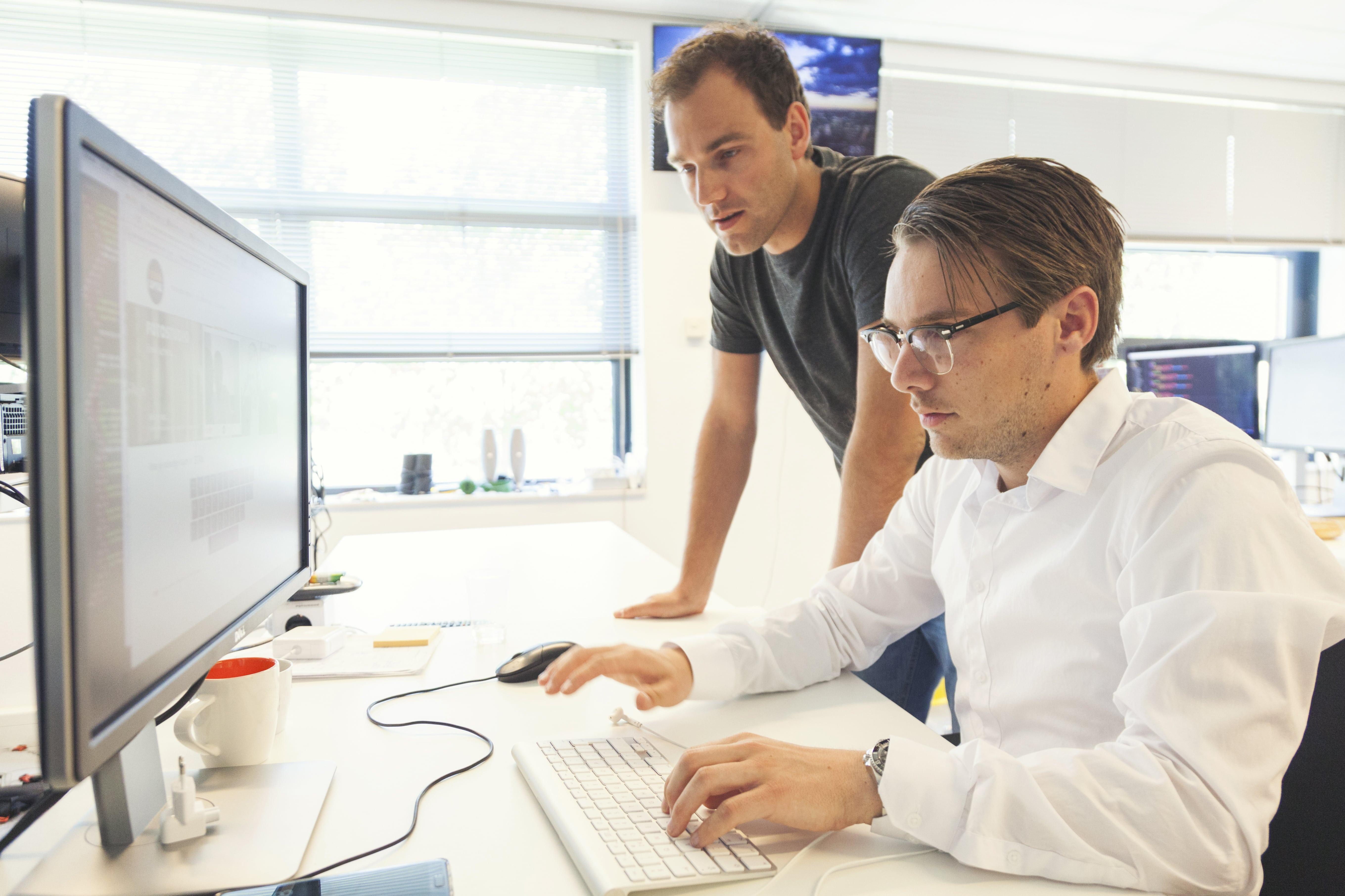 Zwei Männer gucken auf einen Computer