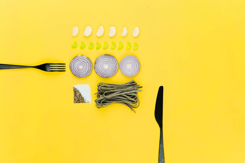 Essen und Besteck liegen auf dem gelben Hintergrund