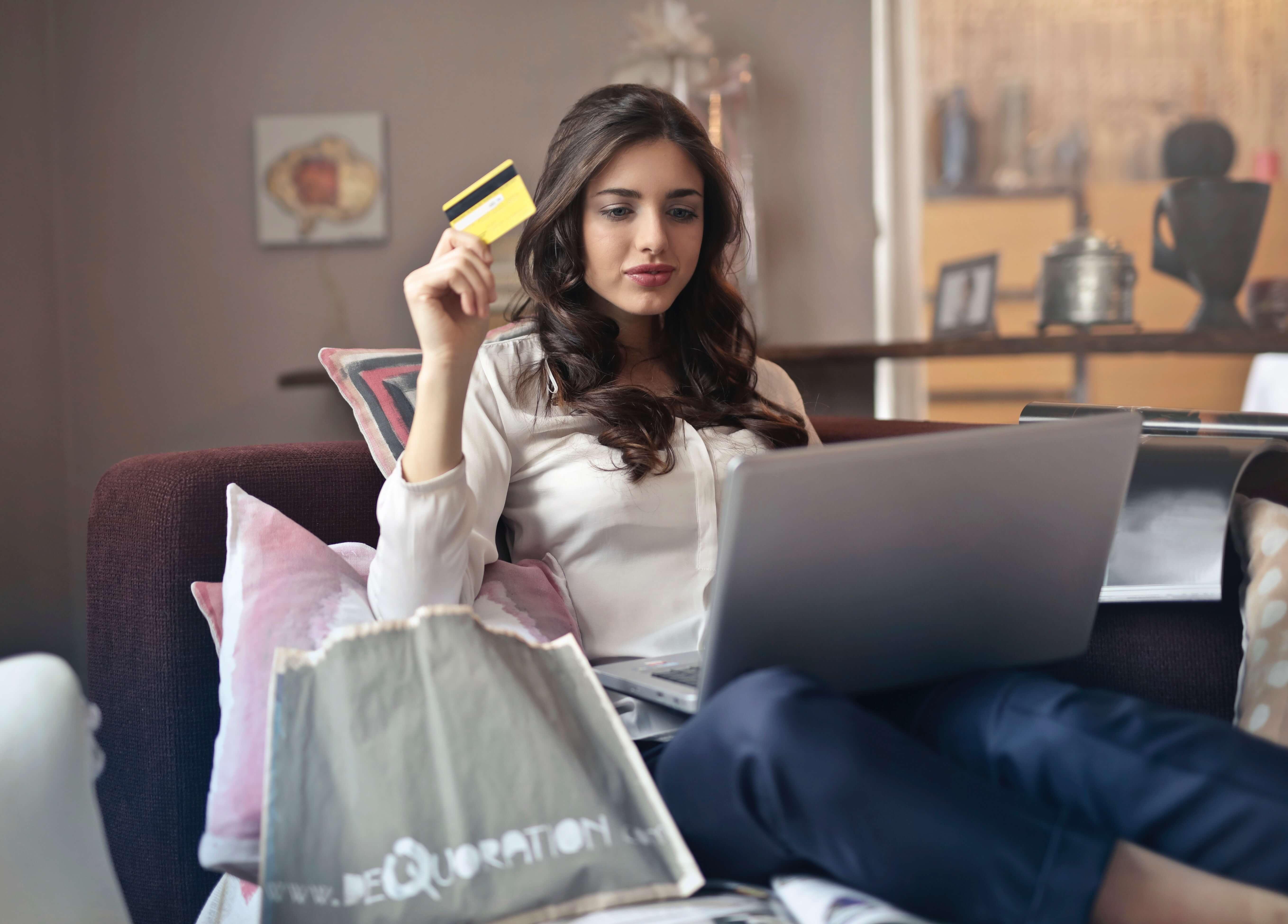 Mädchen sitzt auf dem Sofa mit einem Laptop