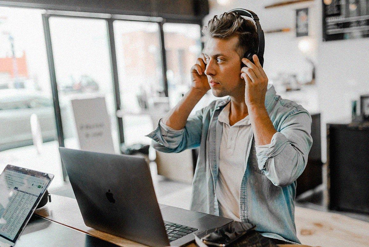 Werkstudent mit Kopfhörer sitzt vor dem Notebook und arbeitet