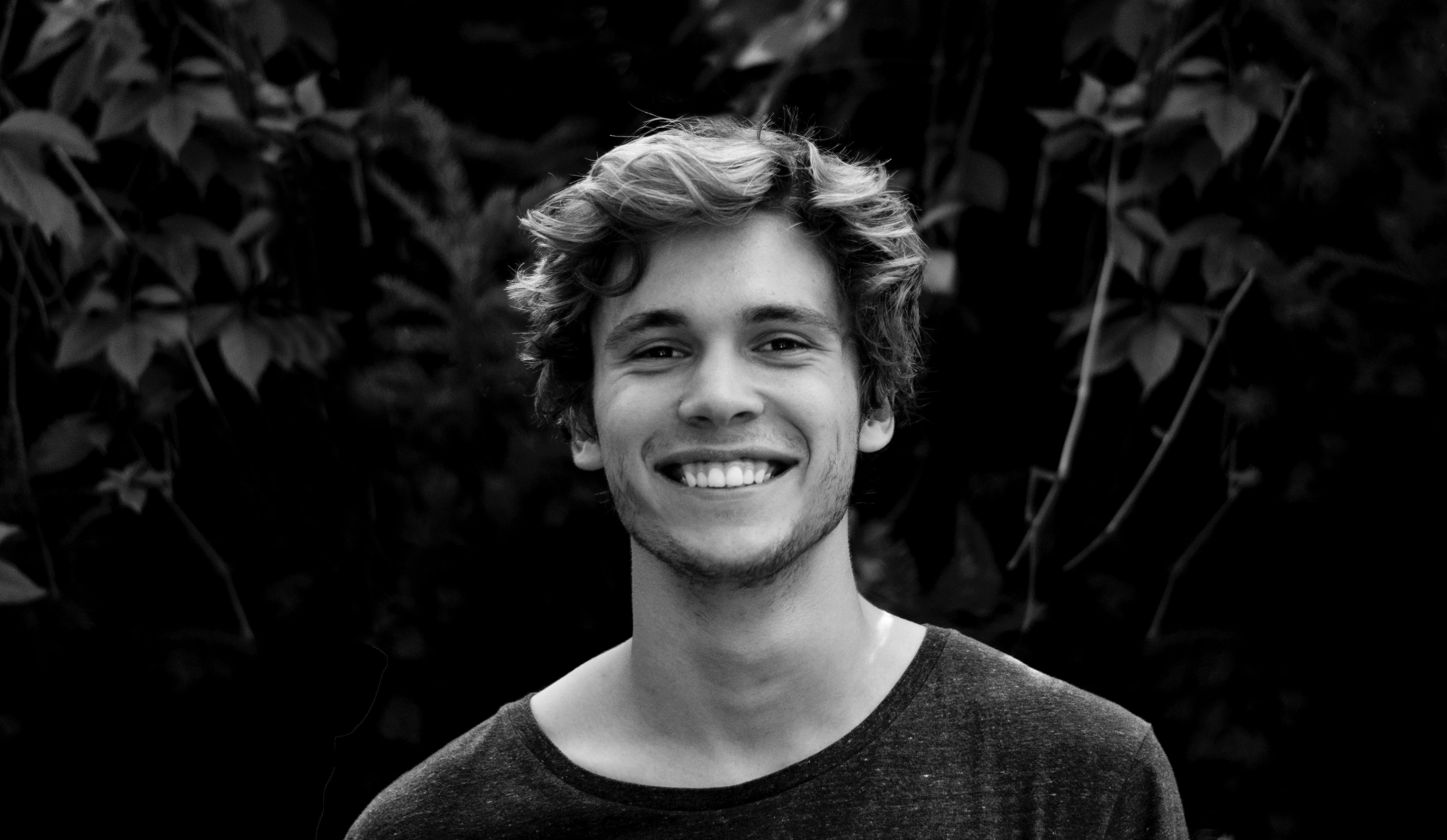 Junger Mann lächelt schwarz weiß