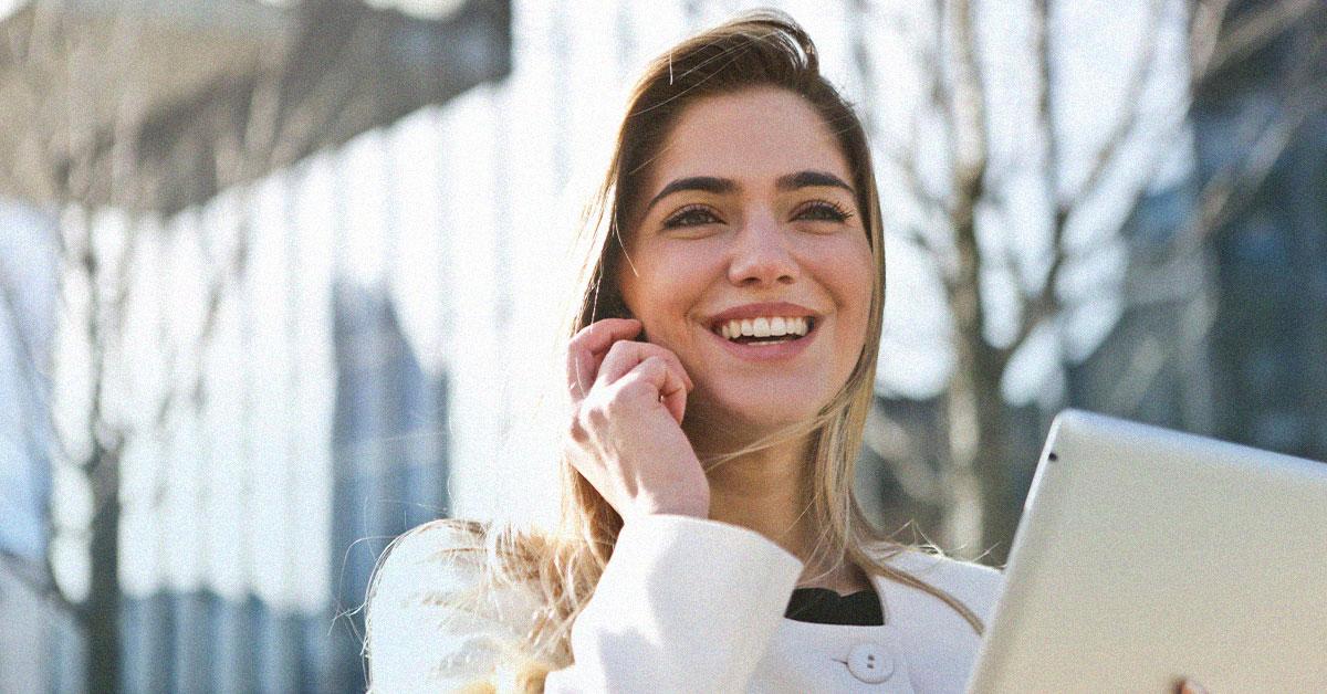 Lachende Frau mit Tablet in der Hand