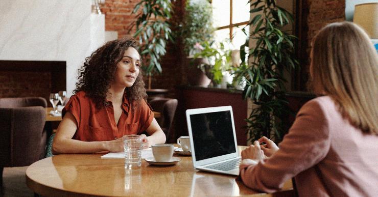 zwei Frauen sitzen im cafe und eine frau hat ihren laptop vor sich