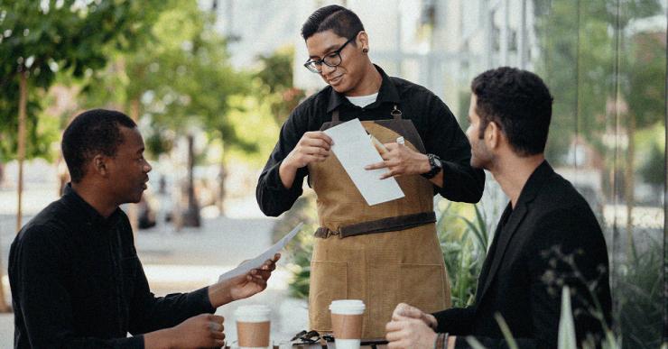 ein kellner zeigt das menue den zwei männlichen gästen