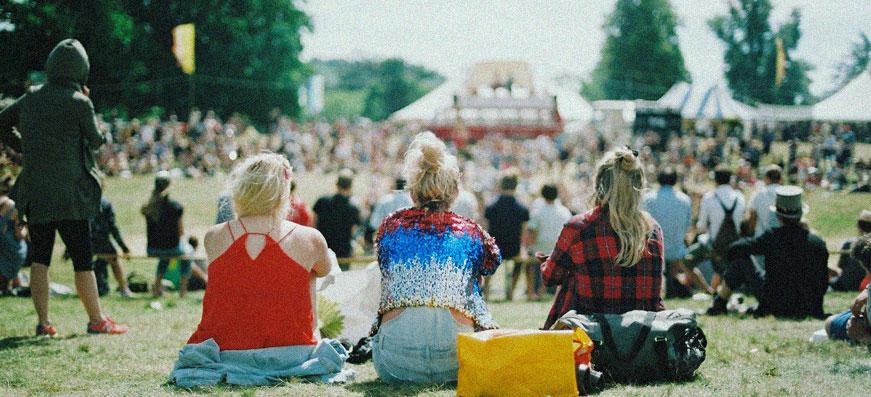 tjejer sitter på gräset på en festival