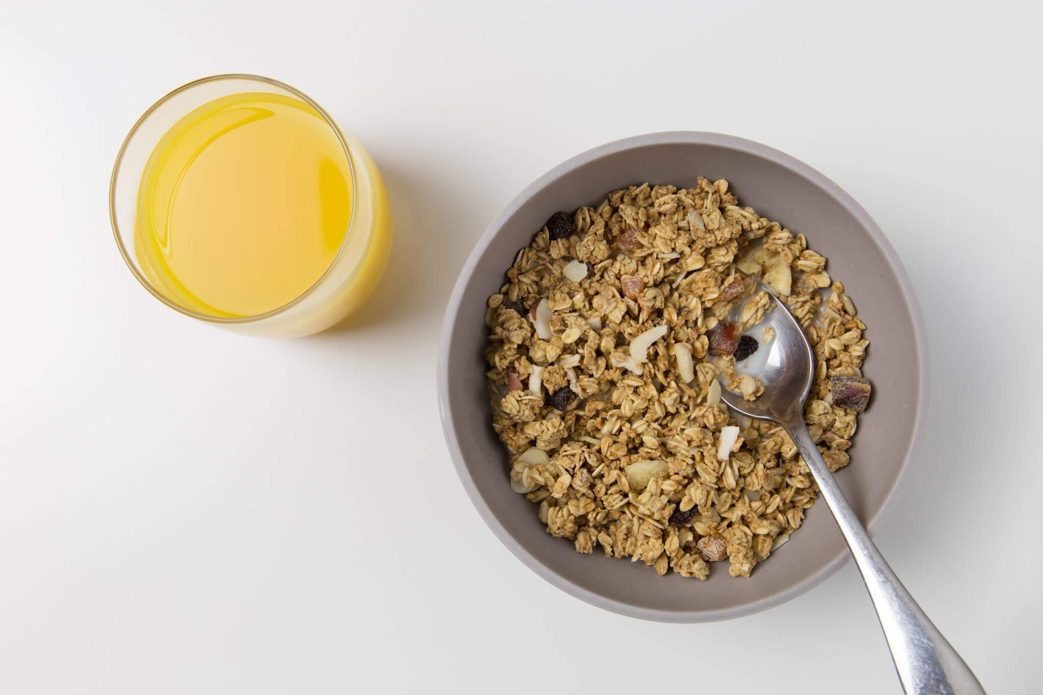 Schüssel mit Müsli und Orangensaft
