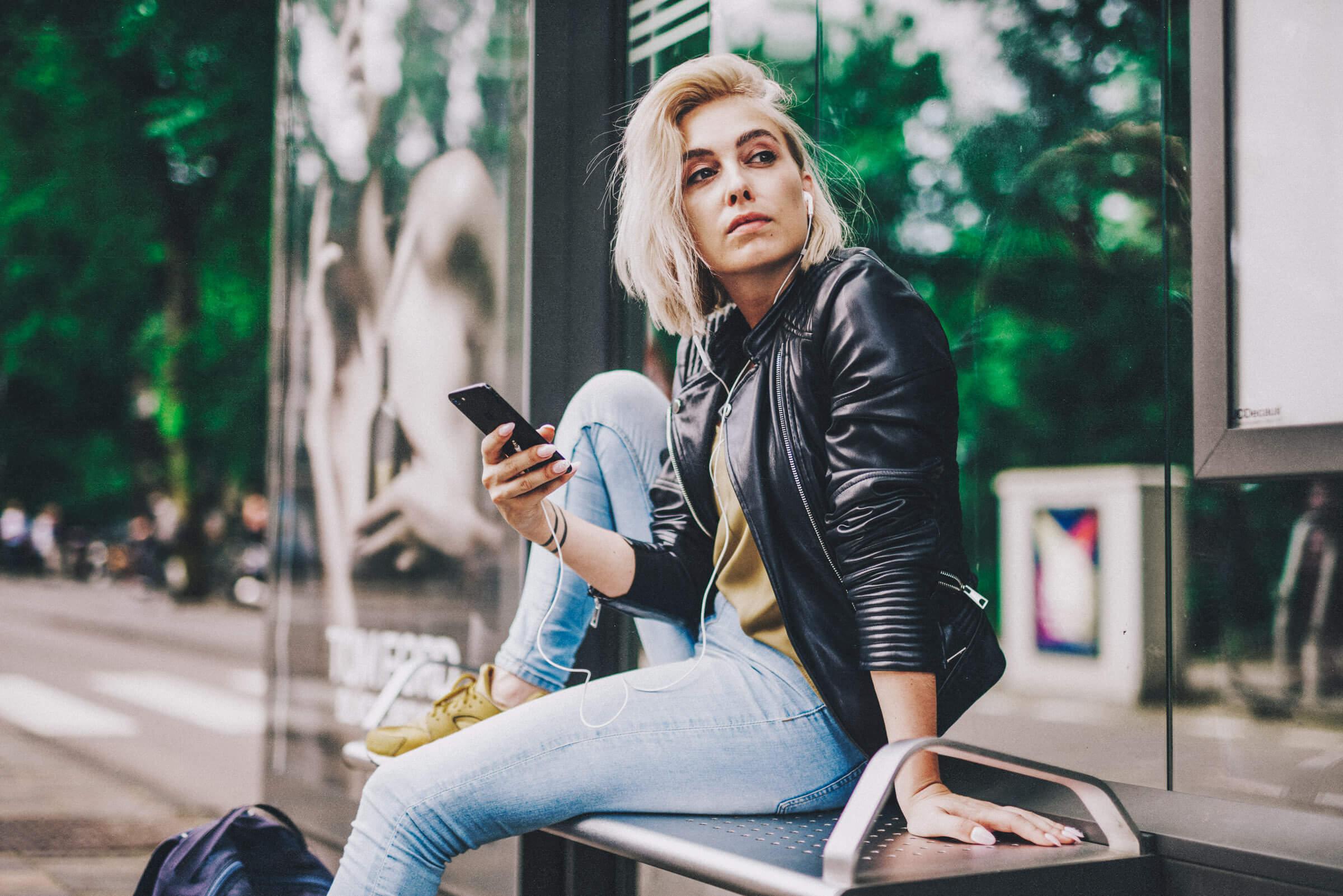 Mädchen sitzt an einer Bushaltestelle