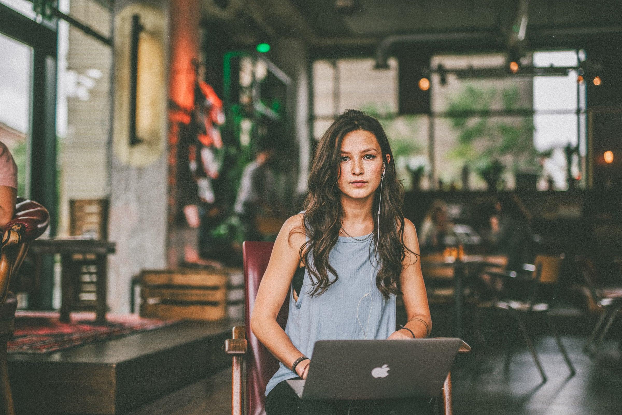 Eine Frau sitzt auf einem Stuhl mit ihrem Laptop auf dem Schoss und einem Kopfhörer im Ohr.