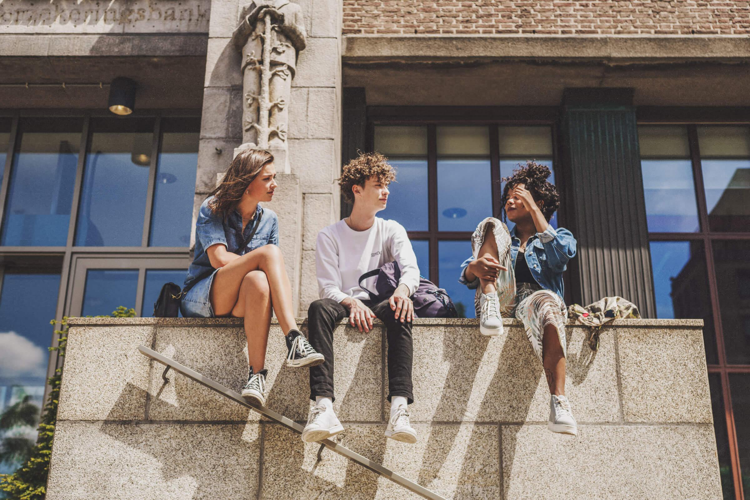 tres amigos hablando subidos en un muro