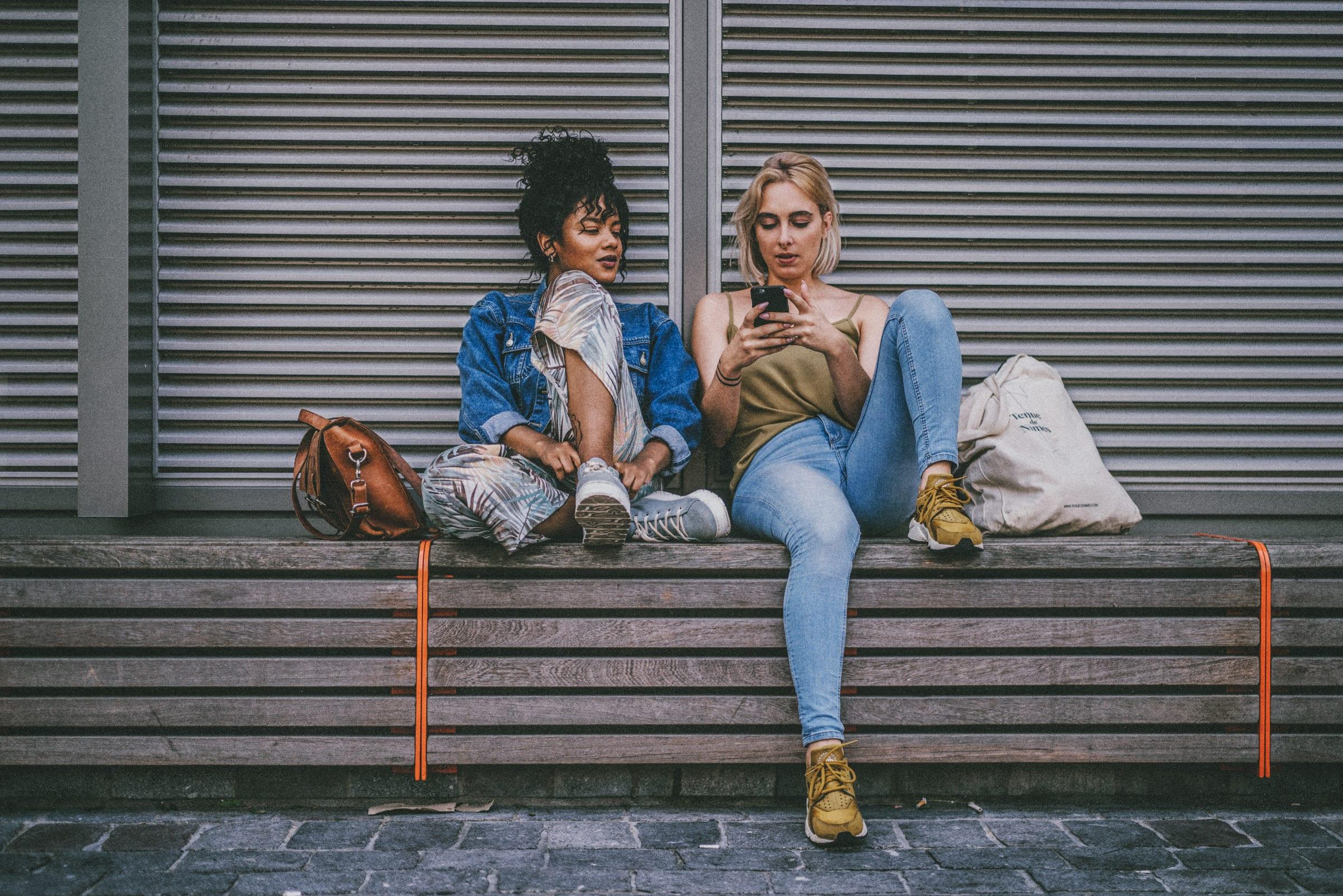 Zwei Frauen sitzen nebeneinander und gucken auf ein Handy.