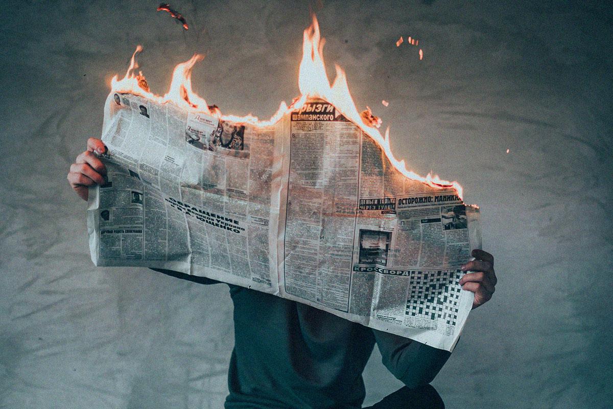 Mann hält brennende Zeitung in den Händen