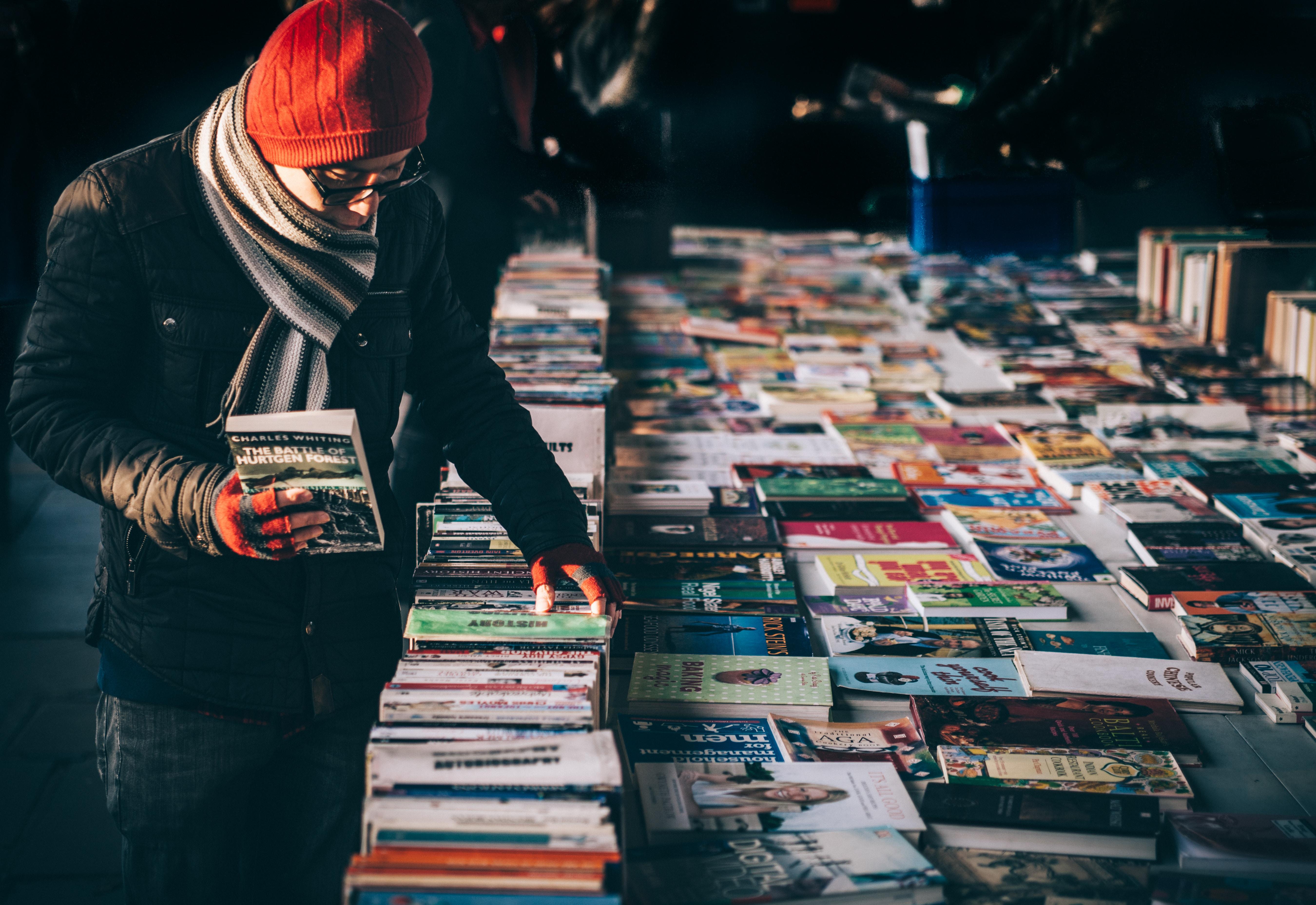 Mann schaut sich Bücher auf Flohmarkt an