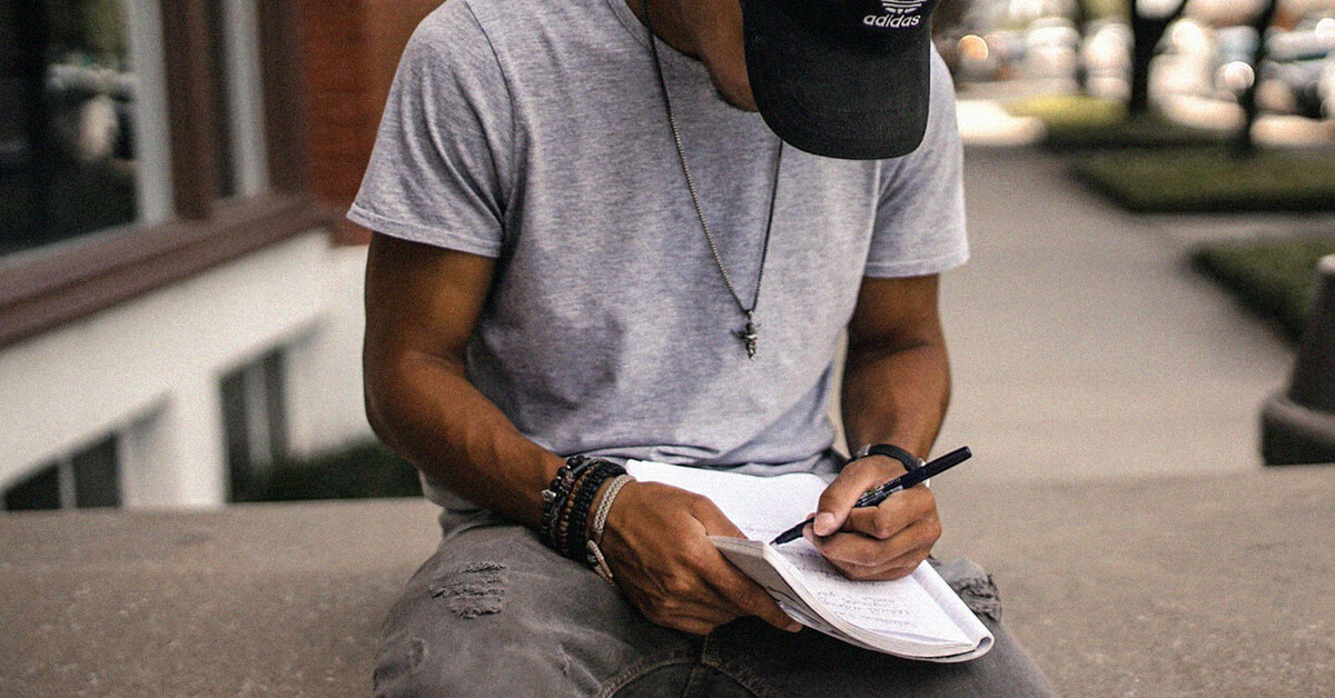 Man writing outside