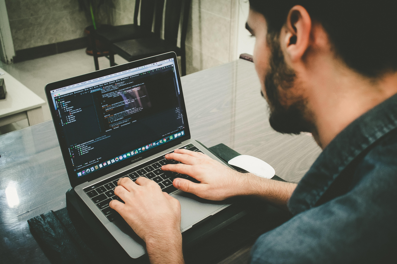 Mann programmiert etwas am Laptop