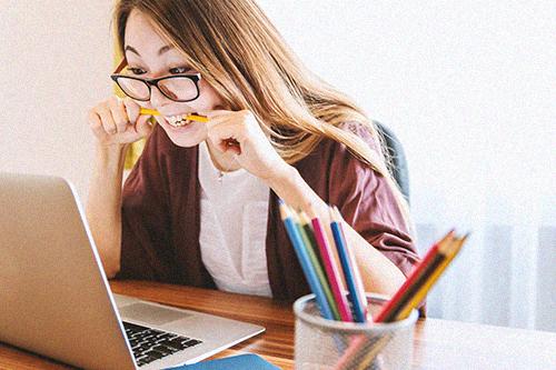 Girl biting pen