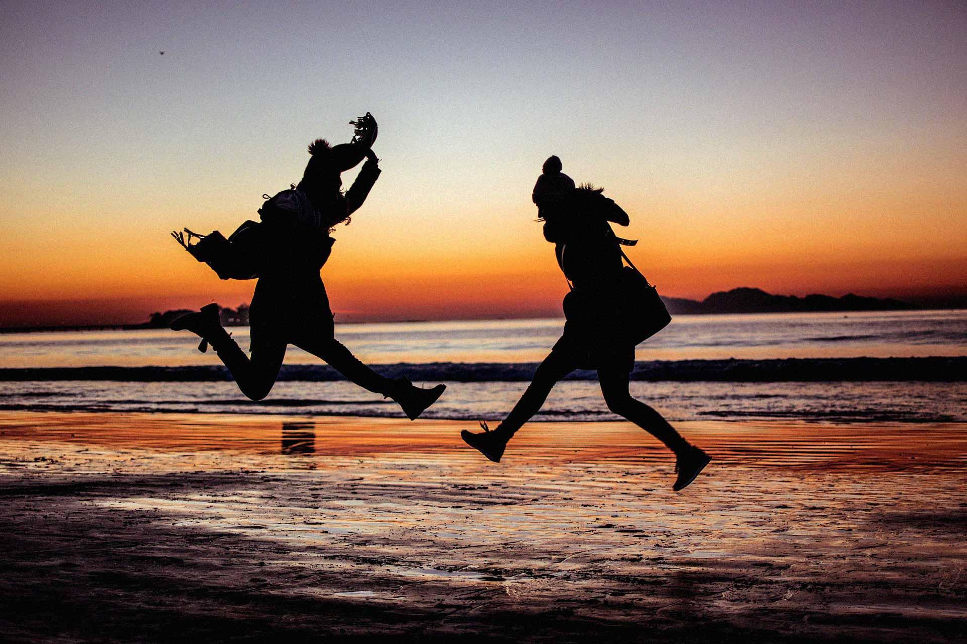 Freunde springen in die Luft mit dem Sonnenuntergang im Hintergrund