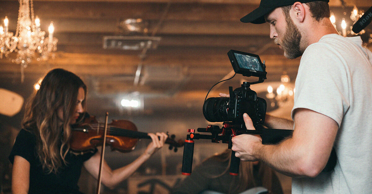 Man videoing a girl playing the violin