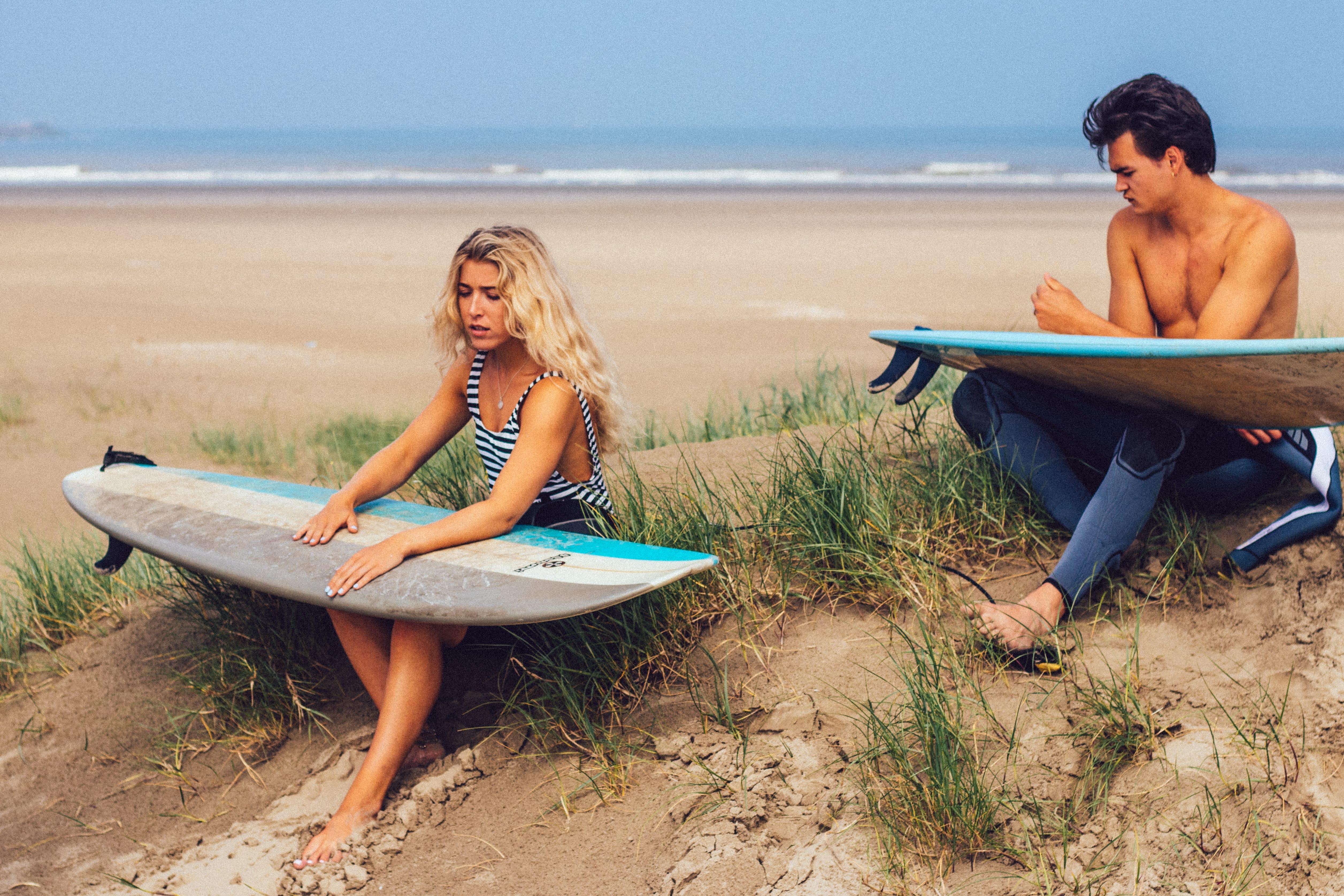 Eine Frau und ein Mann sitzen mit Surfboards am Strand