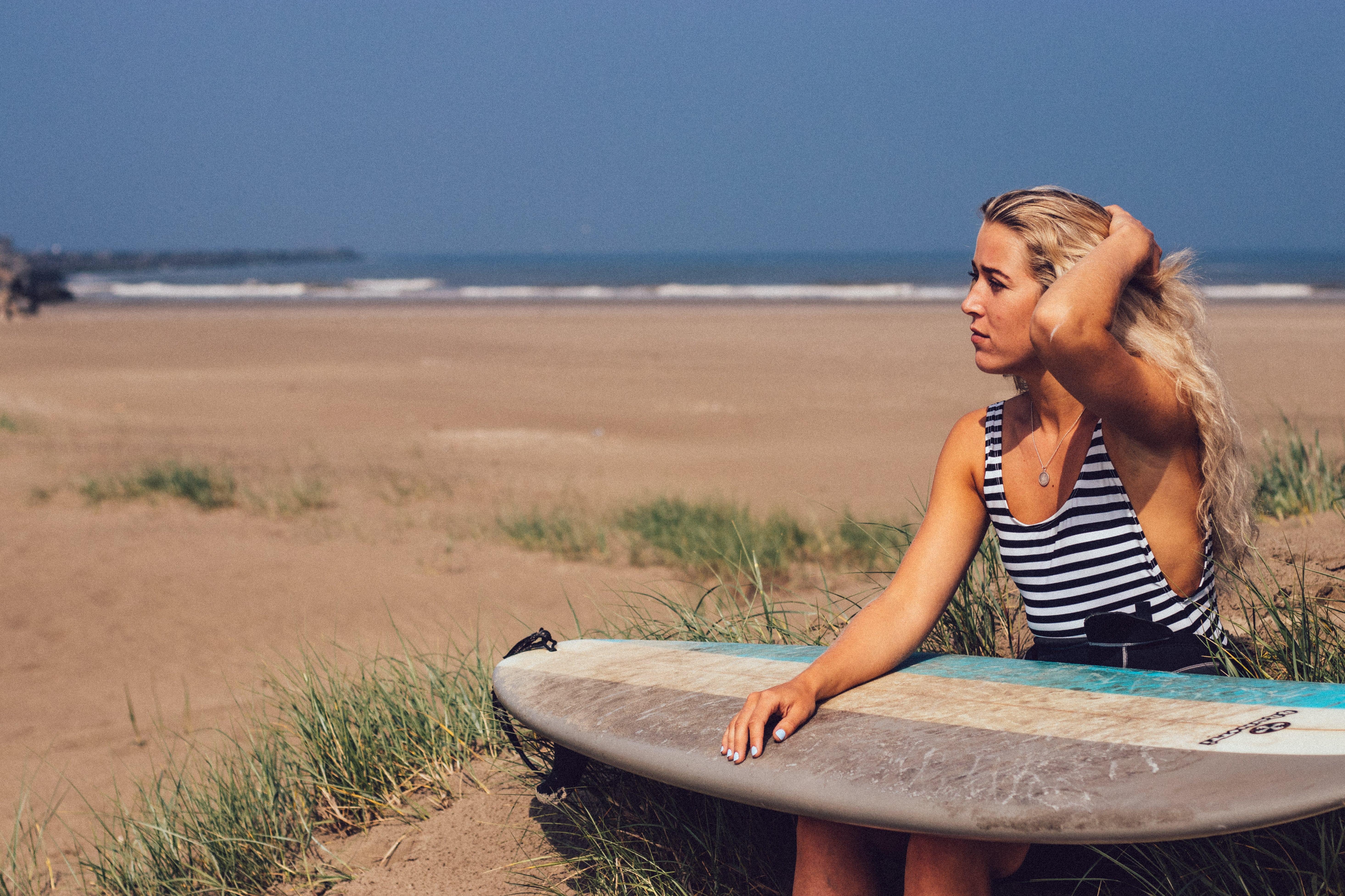 Frau sitze am Strand mit Surfbord in der Hand