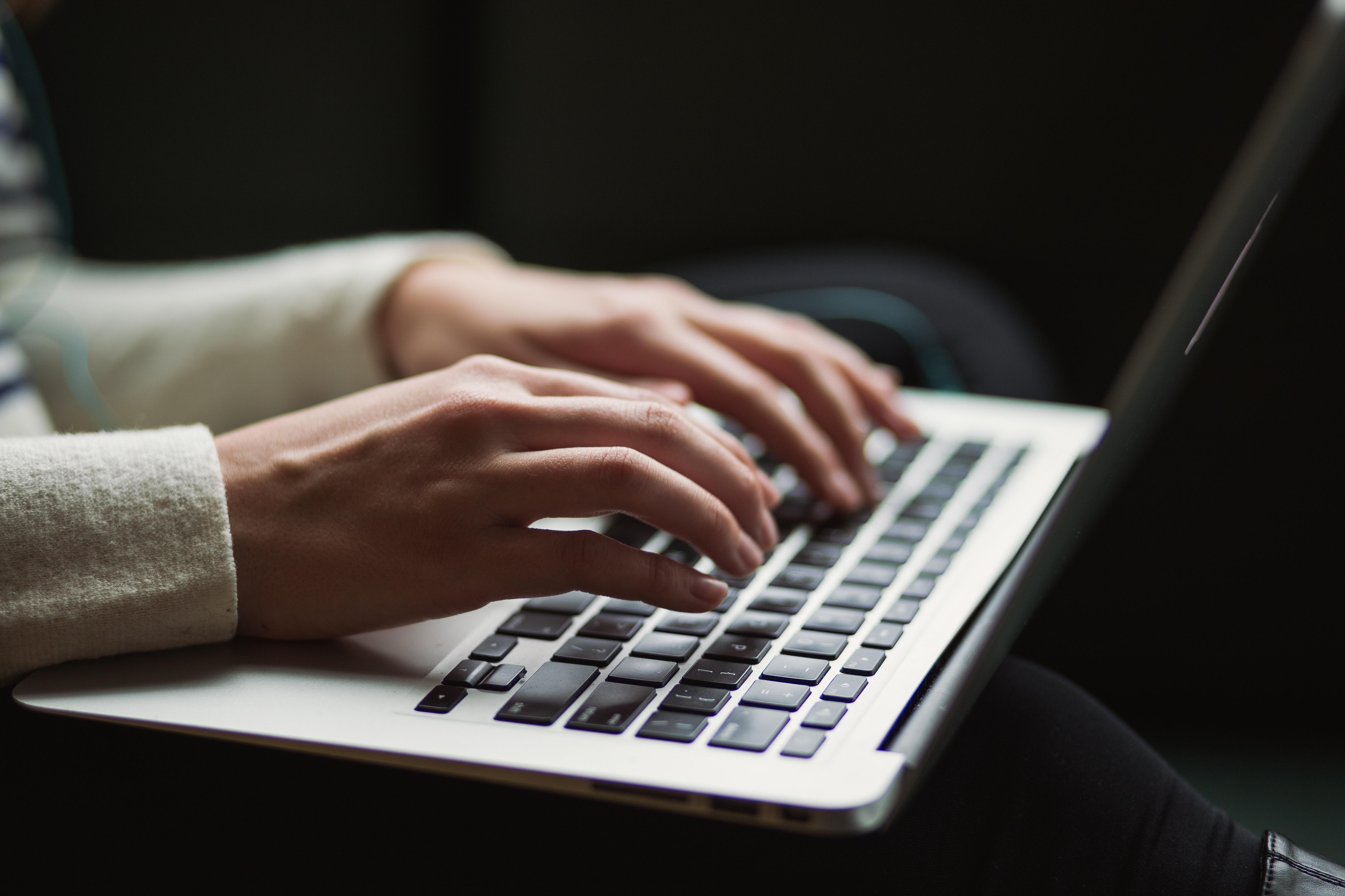 Frau tippt auf seinem Laptop