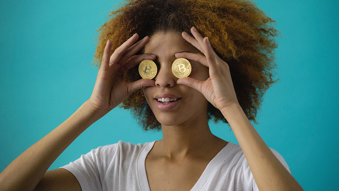 Browned haired girl holding coins in front of eyes