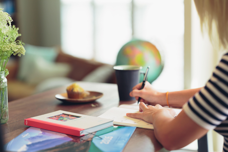 Frau schreibt in ihr Notizbuch. Auf dm Tisch liegen Bücher, eine Kaffeetasse, ein Muffin und ein Globus.