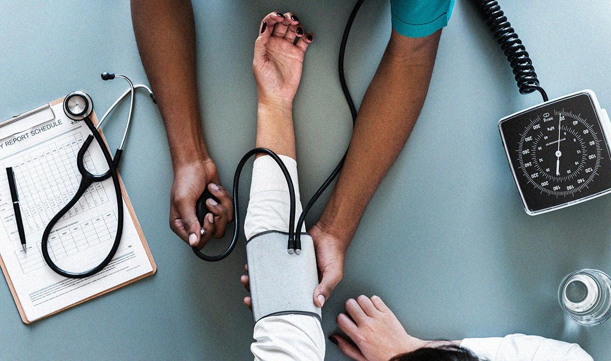 Arzt am Messen des Blutdruckes eines Patienten