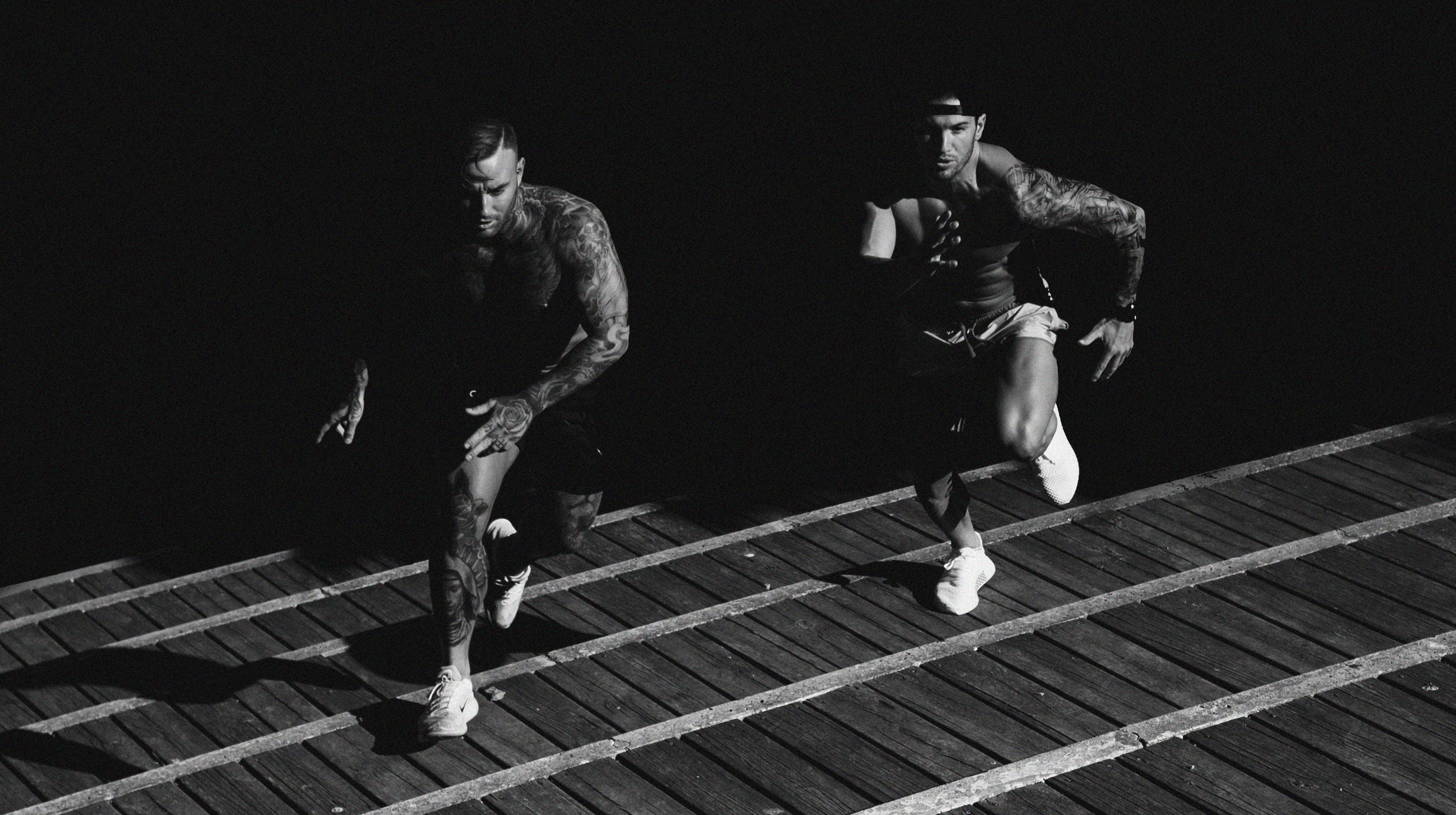 Black and white photo of two men running