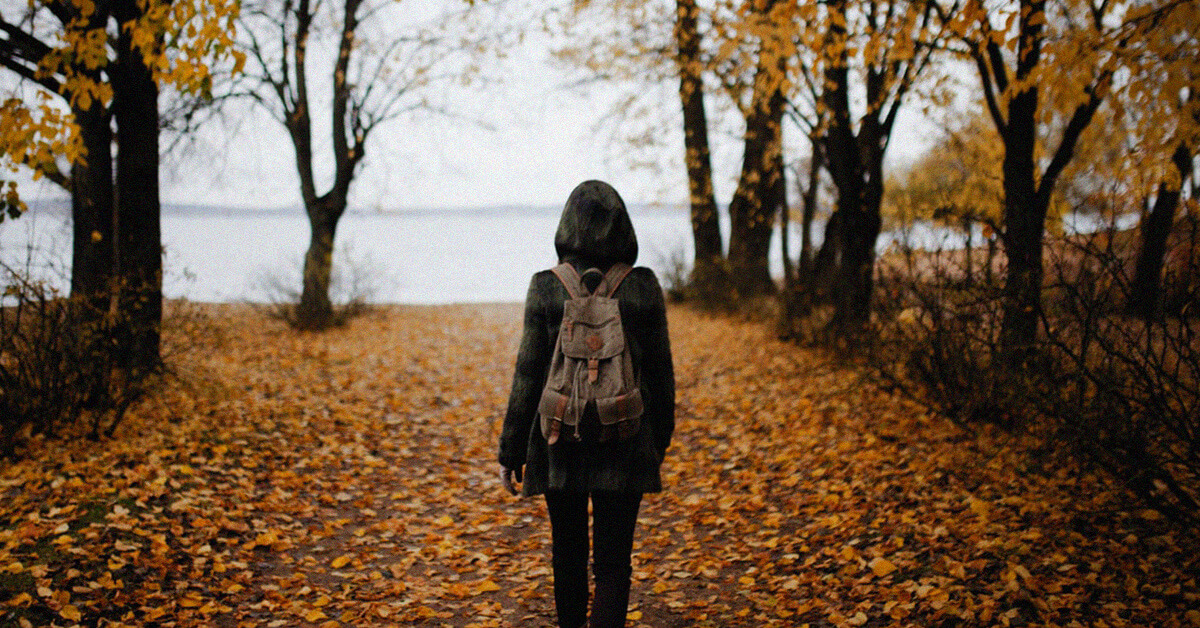 Girl walking through autumn trees