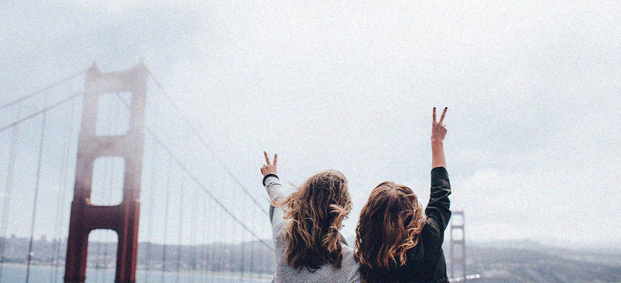 Two girls in front of a bridge