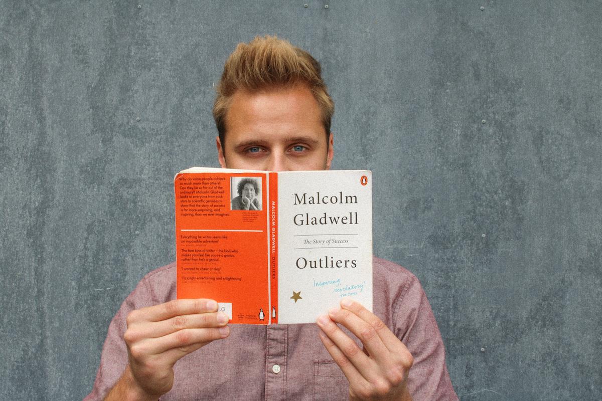 Mann mit Buch vor einer grauen Wand