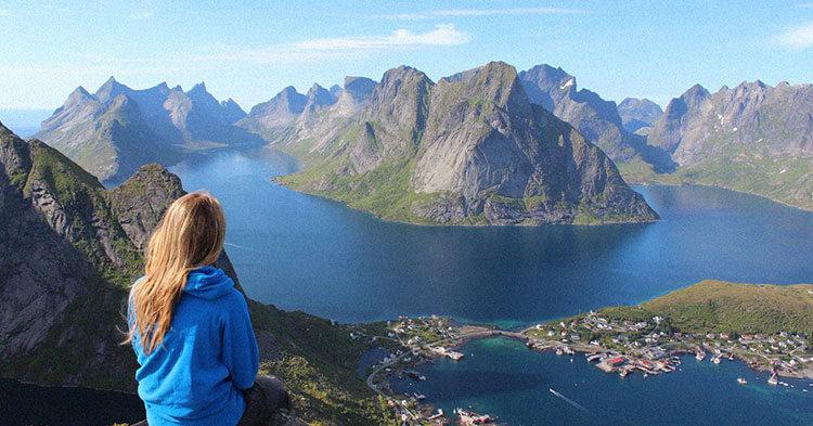 Frau, die auf dem Gipfel eines Bergs sitzt und ins Tal schaut