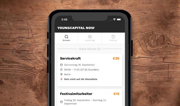 Auf einem Handy ist die YoungCapital NOW App offen und zeigt eine Stellen als Servickraft und Festivalmitarbeiter an